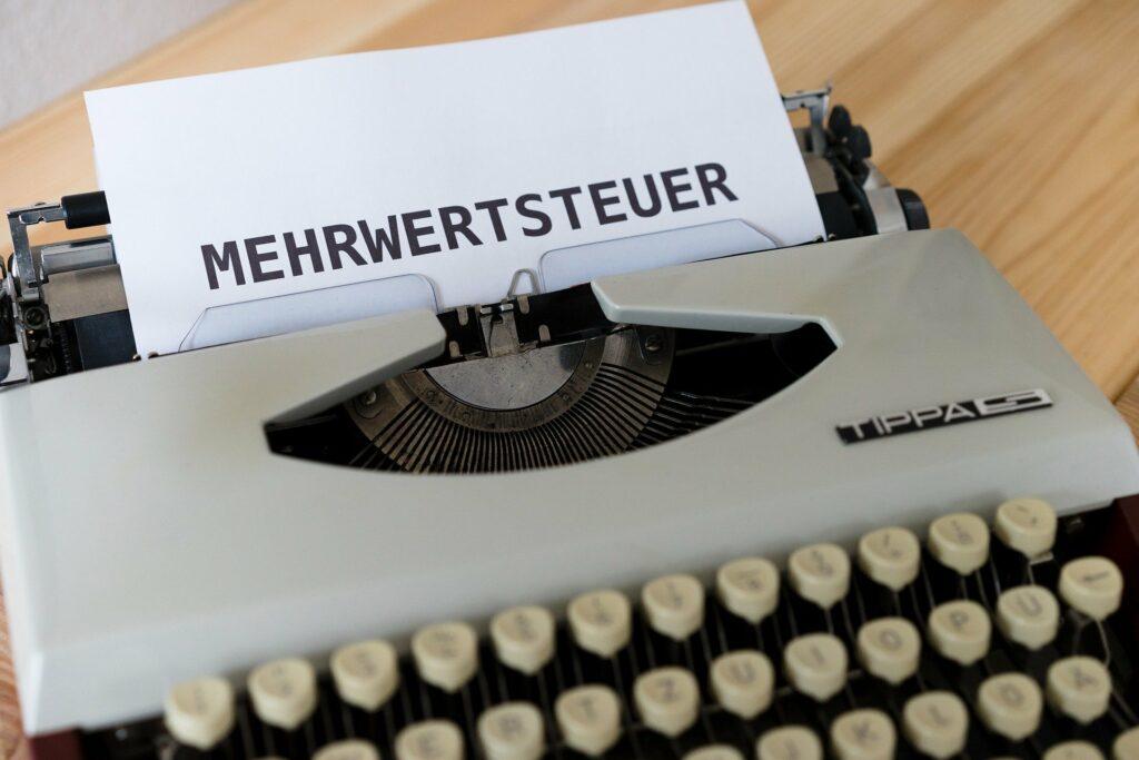 Auf einem Blatt Papier in einer Schreibmaschine steht in großen Lettern: Mehrwertsteuer